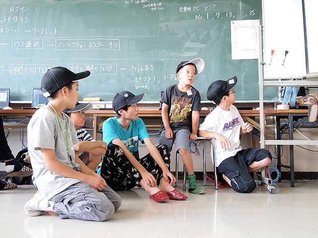黒板の前で座る子どもたち